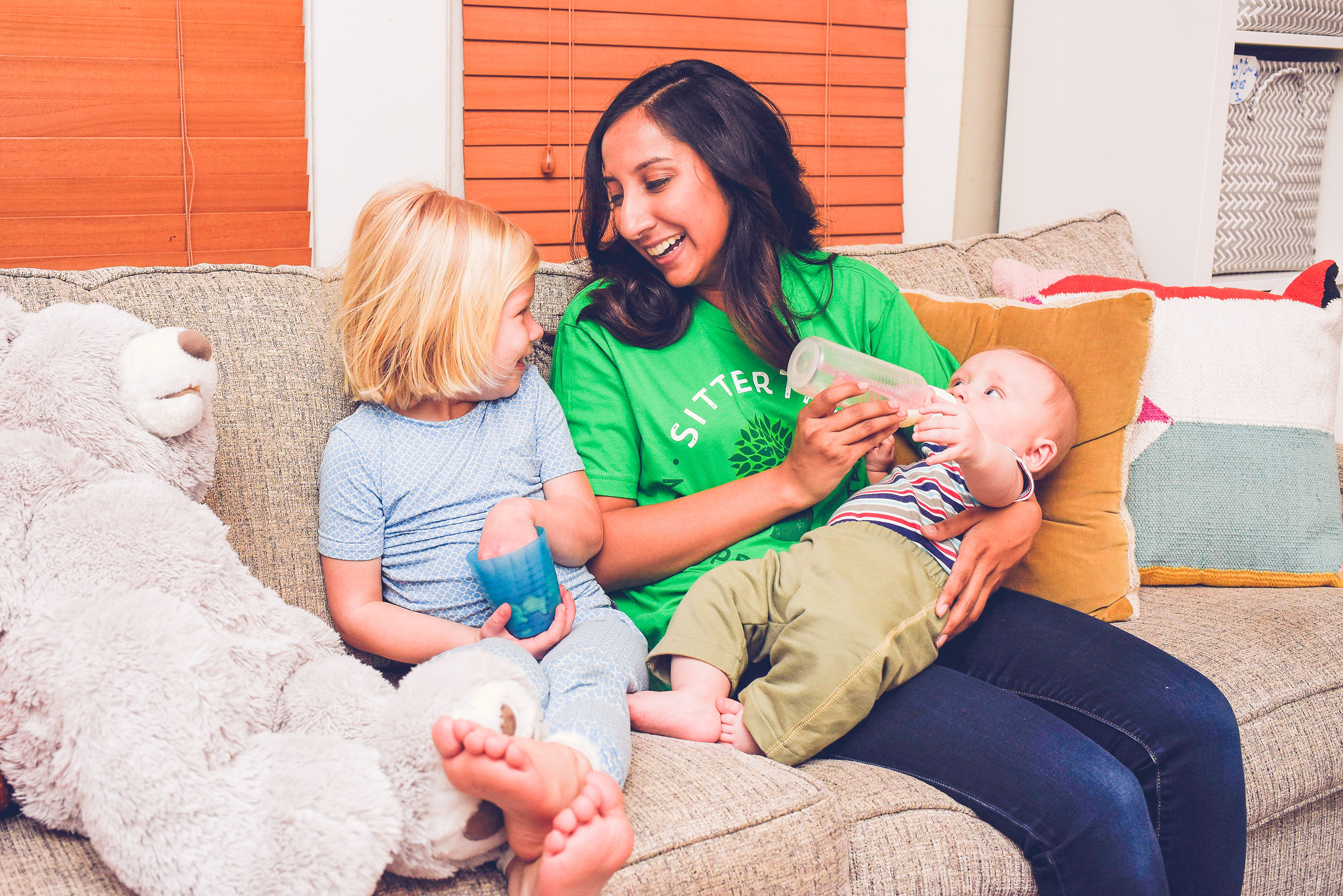 Sitter feeding baby a bottle while talking to toddler