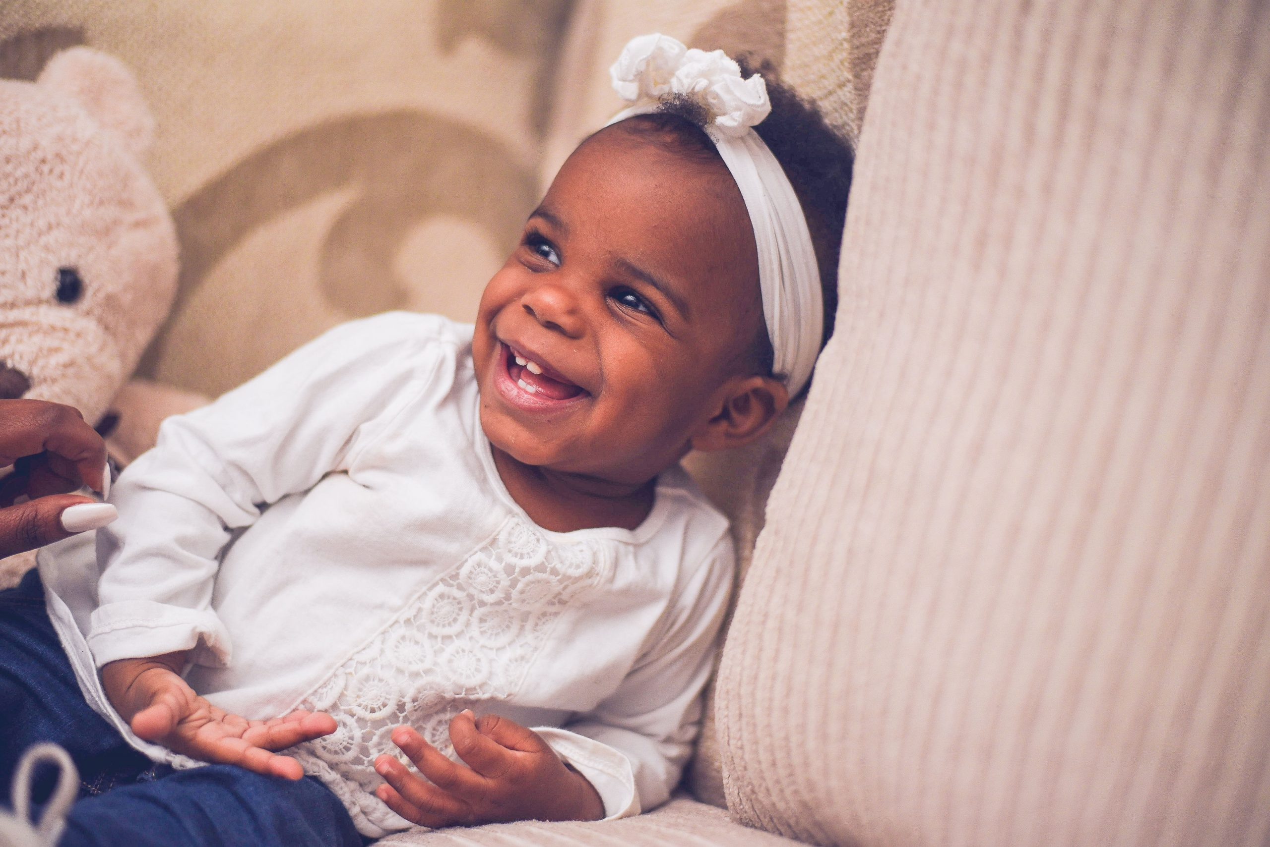 Smiling baby girl with a white bow making eye contact